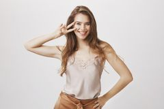 Being opened to any opportunity to have fun. Portrait of beautiful cheerful young woman holding v or victory sign near. Face, smiling broadly, standing with Royalty Free Stock Photos