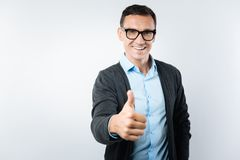 Joyful smart man showing thumbs up gesture Royalty Free Stock Photography