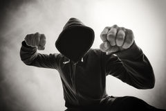 Being punched and mugged by aggressive violent man on street. Street agression, being punched and mugged by aggressive violent man in hooded jacket on street Royalty Free Stock Photos