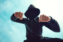 Being punched and mugged by aggressive violent man on street. Being punched and mugged by aggressive violent man in hooded jacket on street, victim's pov Royalty Free Stock Image
