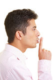 Being quiet. Man putting his index finger on his lips Royalty Free Stock Image