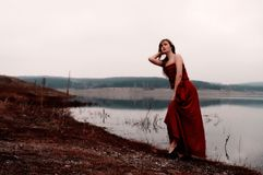 Beautiful woman in red dress is coming out of the lake Royalty Free Stock Images
