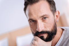 Serious dark-haired grey-eyed man thinking. Being serious. Concentrated bearded dark-haired man of middle age wearing a white shirt and an earring and touching Stock Photos