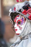 Being unnoticed. Schwaebisch-Hall, Germany - February 23, 2014 - Woman, dressed up in a Venetian style costume with a colorful mask attends the Hallia Venetia Royalty Free Stock Photography
