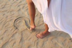Beinmädchen zeichnet in das Sandherz Lizenzfreies Stockfoto