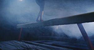 Beinspringen Berufsmädchenturner in Zeitlupe im Rauche auf dem Schwebebalken Die künstlerische Gymnastik der Frauen stock footage
