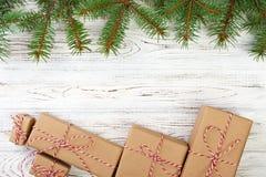 A beira bonita do feriado do Natal com os presentes decorativos amarrados com fita e curvas vermelhas no pinho fresco ramifica em Fotografia de Stock