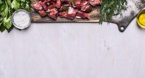 Beira com as ervas cortadas cruas frescas de sal do óleo do talhador de carne do cordeiro na bandeira rústica de madeira branca d Fotos de Stock
