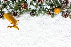 Beira da árvore de abeto do Natal com neve, rena e pisco de peito vermelho Imagens de Stock