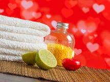 A beira da massagem dos termas com toalha empilhou a vela e o cal vermelhos para o dia de são valentim Imagens de Stock Royalty Free