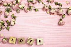 A beira de flores cor-de-rosa e a palavra amam no backgrou de madeira cor-de-rosa Imagens de Stock