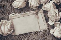 Beira de rosas brancas secas, pilha de cartão velhos, imagem do sepia imagem de stock