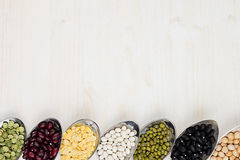 A beira decorativa da variedade pulsa feijões nas colheres com espaço da cópia no fundo de madeira branco Fotos de Stock