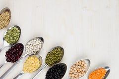 A beira decorativa da variedade pulsa feijões nas colheres com espaço da cópia no fundo de madeira branco Imagens de Stock