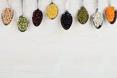 Beira decorativa de feijões diferentes da variedade nas colheres com espaço da cópia no fundo de madeira branco Fotografia de Stock
