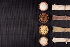 Beira decorativa de macarronetes crus dos pacotes com o ingrediente em umas bacias de madeira no fundo listrado preto da esteira  Fotografia de Stock