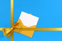 Beira do fundo do presente do Natal com curva do ouro, o cartão vazio e o envelope, espaço da cópia Fotografia de Stock