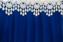 Beira do laço branco sobre a tela azul dobrada Fotografia de Stock Royalty Free