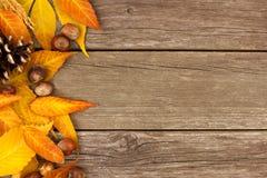 Beira do lado da folha do outono contra a madeira rústica Foto de Stock