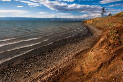 Beira do lago de Baikal com as montanhas no fundo e as nuvens e a luz bonitas imagens de stock royalty free