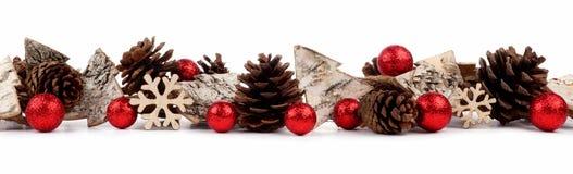 Beira do Natal com os ornamento da árvore, as quinquilharias rústicas e os cones de madeira do pinho isolados sobre o branco