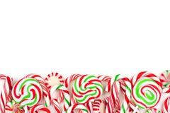 Beira dos doces do Natal com pirulitos, e bastões de doces sobre o branco Foto de Stock