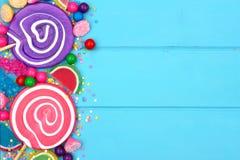 Beira lateral de doces sortidos coloridos contra a madeira azul Fotos de Stock Royalty Free