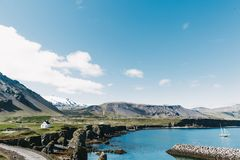 beira-mar bonito com o iate de flutuação na água, na estrada, em montanhas rochosas e em casas na costa no gatklettur, arnarstapi Fotos de Stock