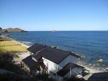 Beira-mar rochoso da costa do campo japonês com construção e campos imagem de stock royalty free