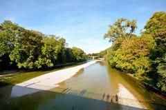 Beira-rio com a ponte através do rio de Isar em Munich, Baviera Alemanha Imagens de Stock Royalty Free