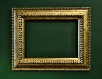 Beira vazia do frame de retrato do ouro na parede verde Foto de Stock Royalty Free