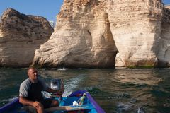 BEIRUT, DER LIBANON - 14. AUGUST 2014: Unbekannter Mann auf einem Boot im Mittelmeer nahe den berühmten Tauben-Felsen lizenzfreie stockfotografie