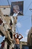 Beirut: Junge unter Spitzenpolitikerplakat im shatila lizenzfreie stockfotografie