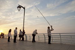 Beirut seafront. People at Beirut seafront. A fisherman is casting is rod over the railings to fish Stock Images
