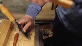 Beitel in de handen van een professionele timmerman de timmerman behandelt de houten hulpmiddelen van het planktimmerwerk 4K stock video