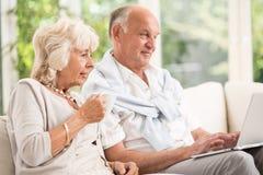 Bejaard echtpaar die laptop met behulp van stock foto's