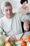 Bejaard gelukkig paar bij keuken Stock Afbeelding