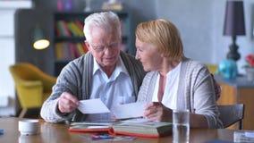 Bejaard gelukkig paar die oud foto album en het glimlachen kijken stock videobeelden
