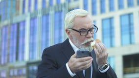 Bejaard mannetje die in kostuum hamburger eten die e-mail, zware baan, gebrek controleren aan tijd stock footage