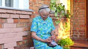 Bejaard ouder vrouwelijk tellingengeld in haar portefeuille stock video