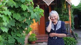 Bejaard ouder wijfje die op telefoon spreken stock video