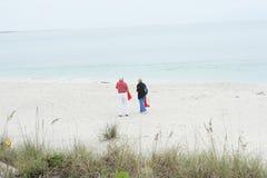 Bejaard paar dat op het strand loopt Stock Fotografie