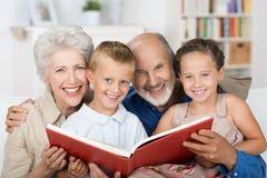 Bejaard paar die aan hun kleinkinderen lezen Royalty-vrije Stock Afbeeldingen