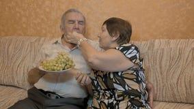 Bejaard paar die druivenbessen eten stock footage