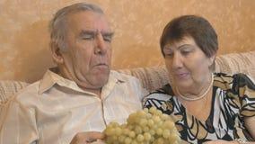 Bejaard paar die druivenbessen eten stock video