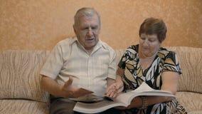 Bejaard paar die een boek, op de laag lezen, zijn zij samen gelukkig stock footage