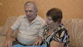 Bejaard paar die een boek, op de laag lezen, zijn zij samen gelukkig stock video