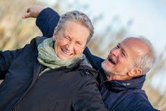 Bejaard paar die en de zon omhelzen vieren Stock Foto
