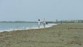 Bejaard paar die langs stormachtige overzees lopen Golven die op leeg zandig strand bespatten stock videobeelden