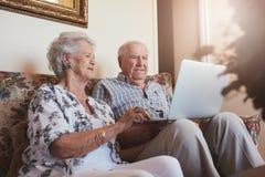 Bejaard paar die laptop thuis met behulp van royalty-vrije stock foto's